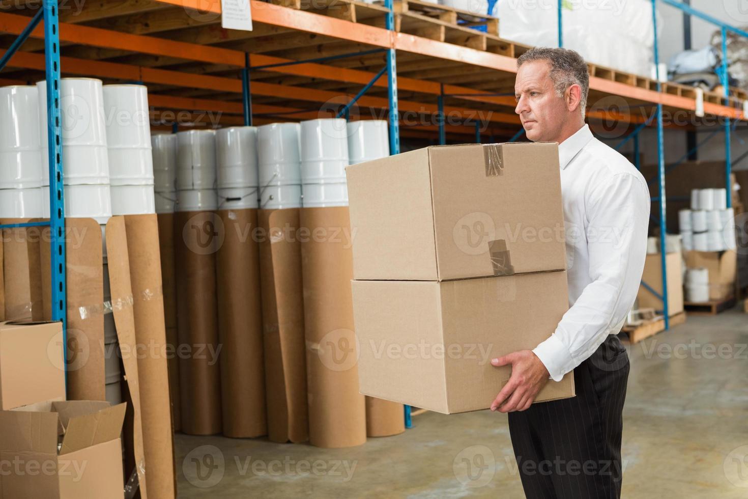responsabile del magazzino che trasporta scatole di cartone foto