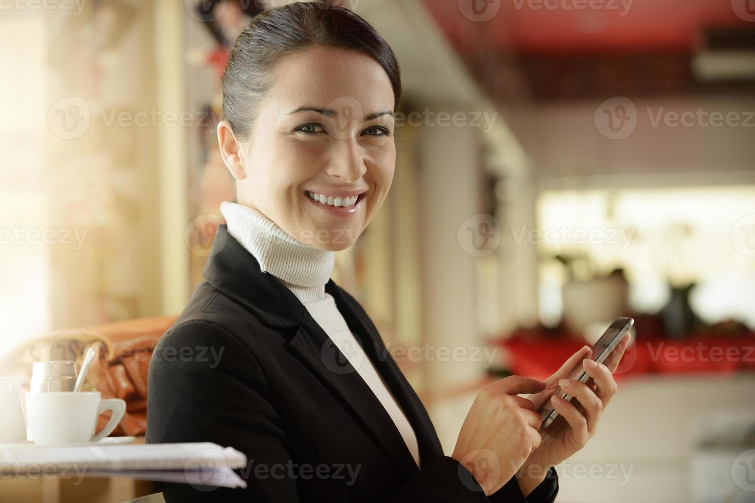 donna al bar che manda un sms con il suo telefono cellulare foto
