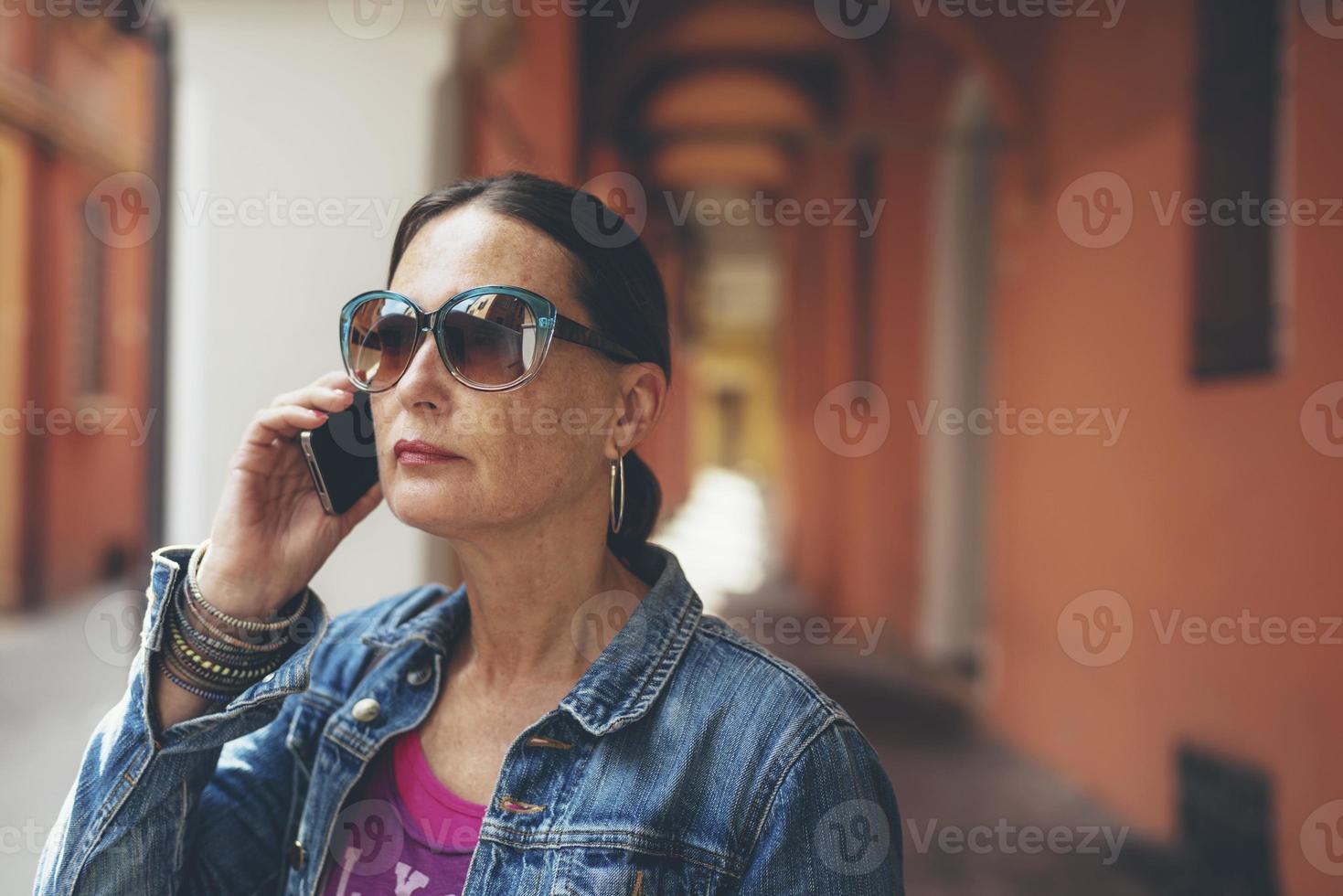 chiamando la donna con gli occhiali da sole nelle strade di bologna, italia. foto