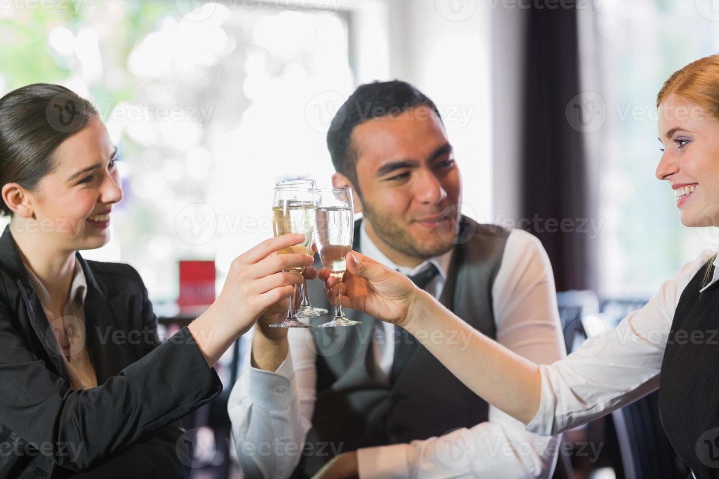felici partner commerciali che celebrano con champagne foto