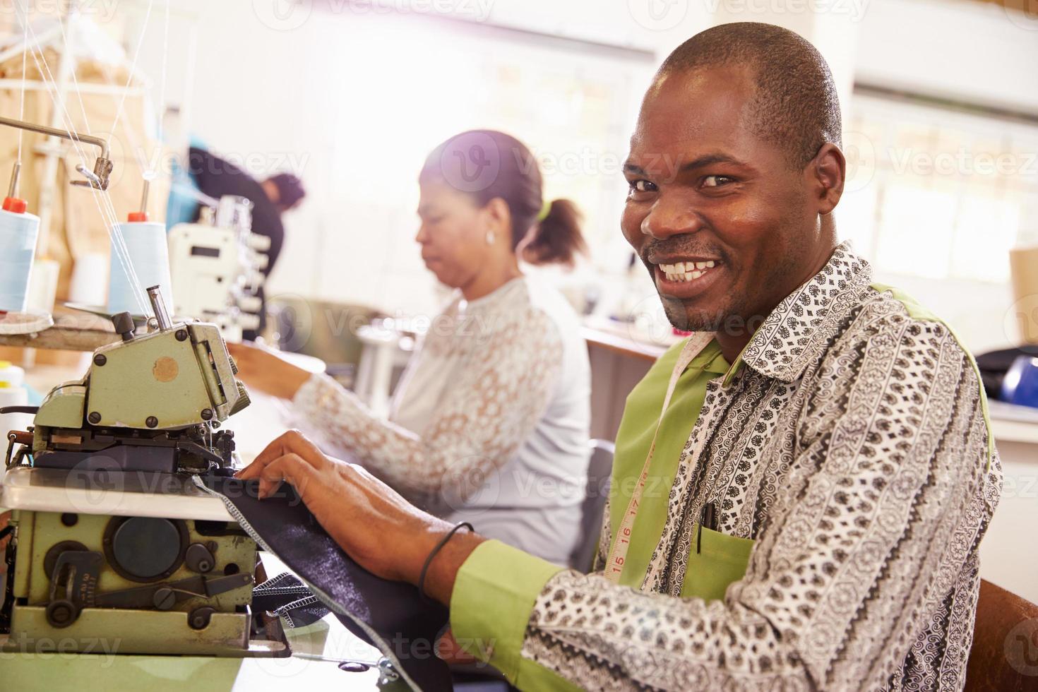 uomo sorridente che cuce in un'officina della comunità, Sudafrica foto