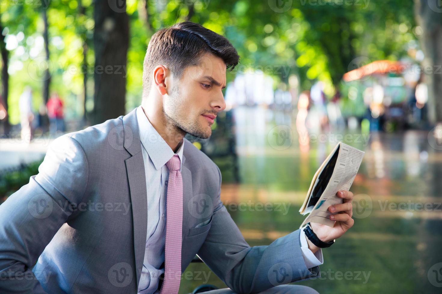 uomo d'affari leggendo il giornale all'aperto foto