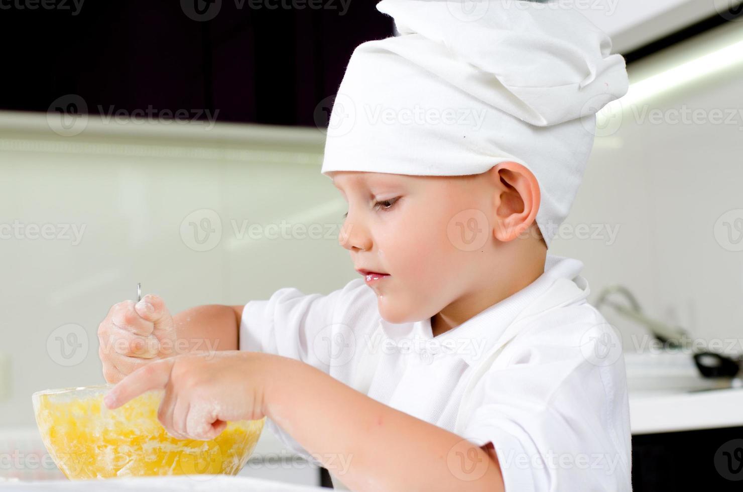simpatico piccolo chef che assaggia la sua cucina foto