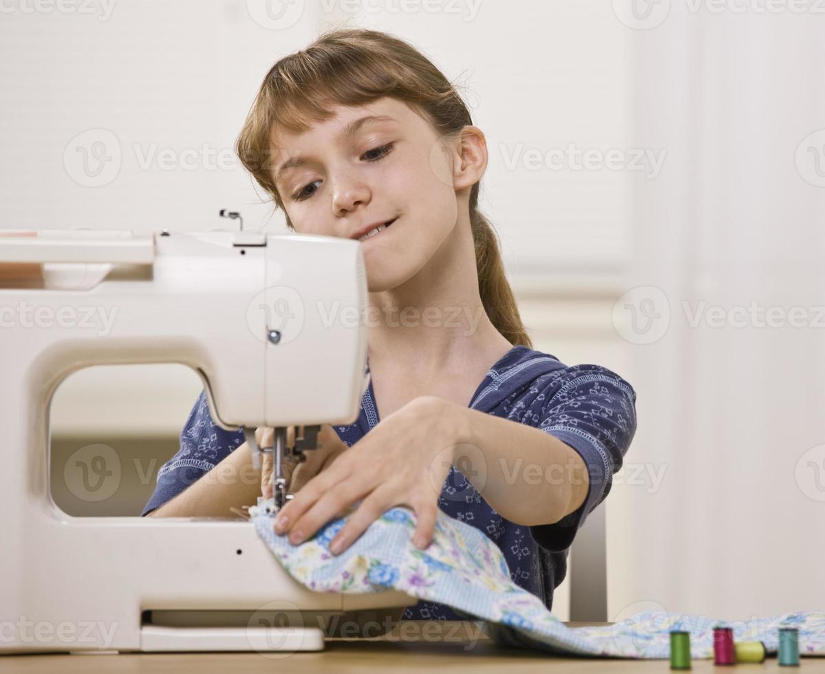 ragazza che usando la macchina da cucire foto