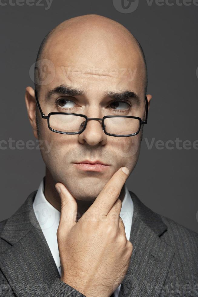 uomo d'affari calvo con gli occhiali con la mano sul mento foto