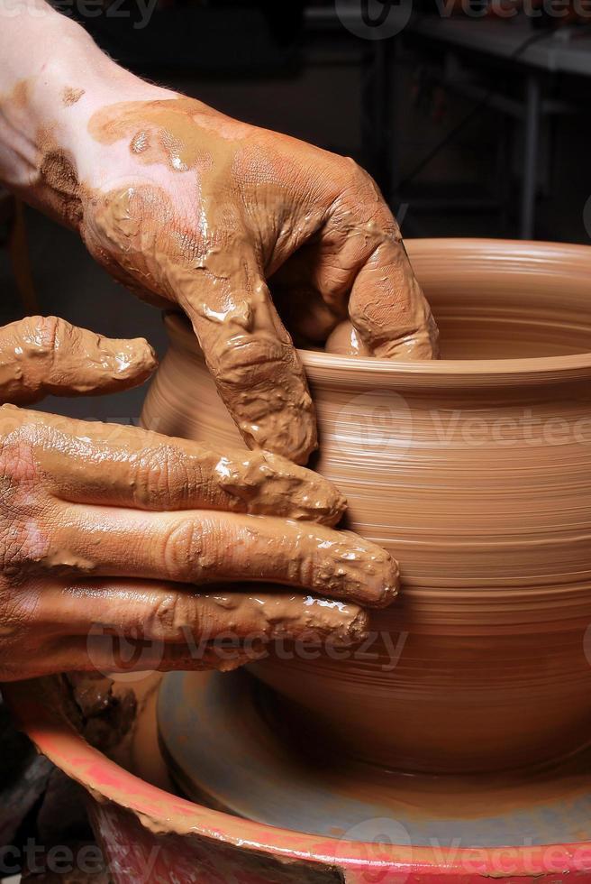 uomo che fa ceramica sulla ruota di ceramica di filatura foto