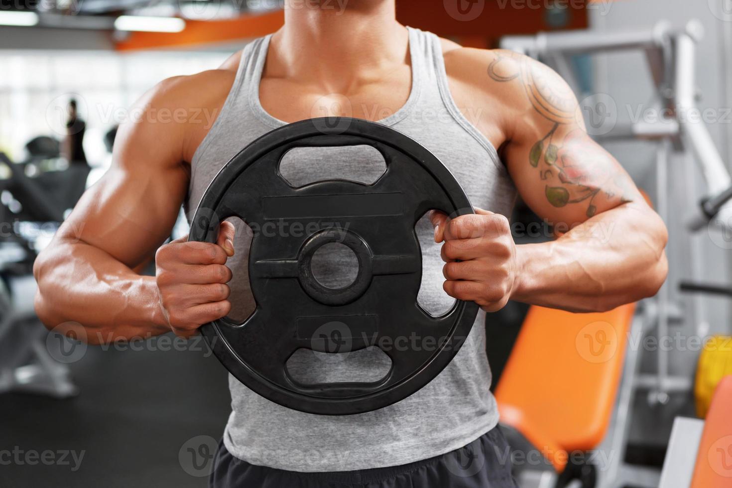 powerlifter con il disco del peso in mano foto