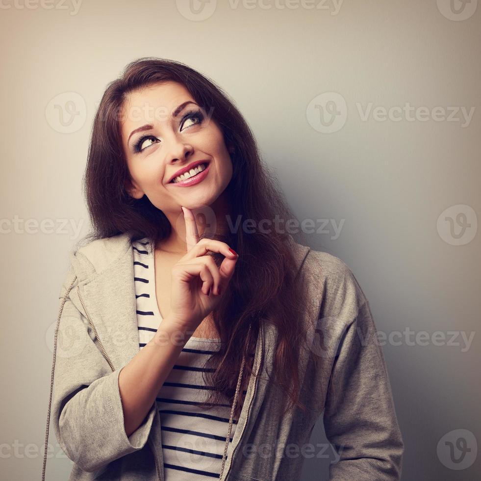 donna felice di pensiero in abbigliamento casual che osserva in su. Vintage ▾ foto