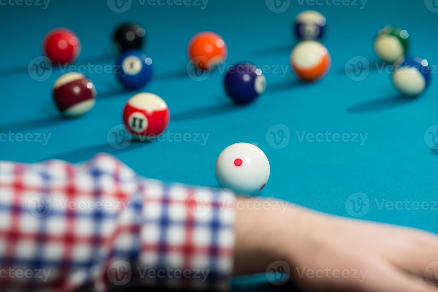 fodera uomo per colpire la palla sul tavolo da biliardo foto