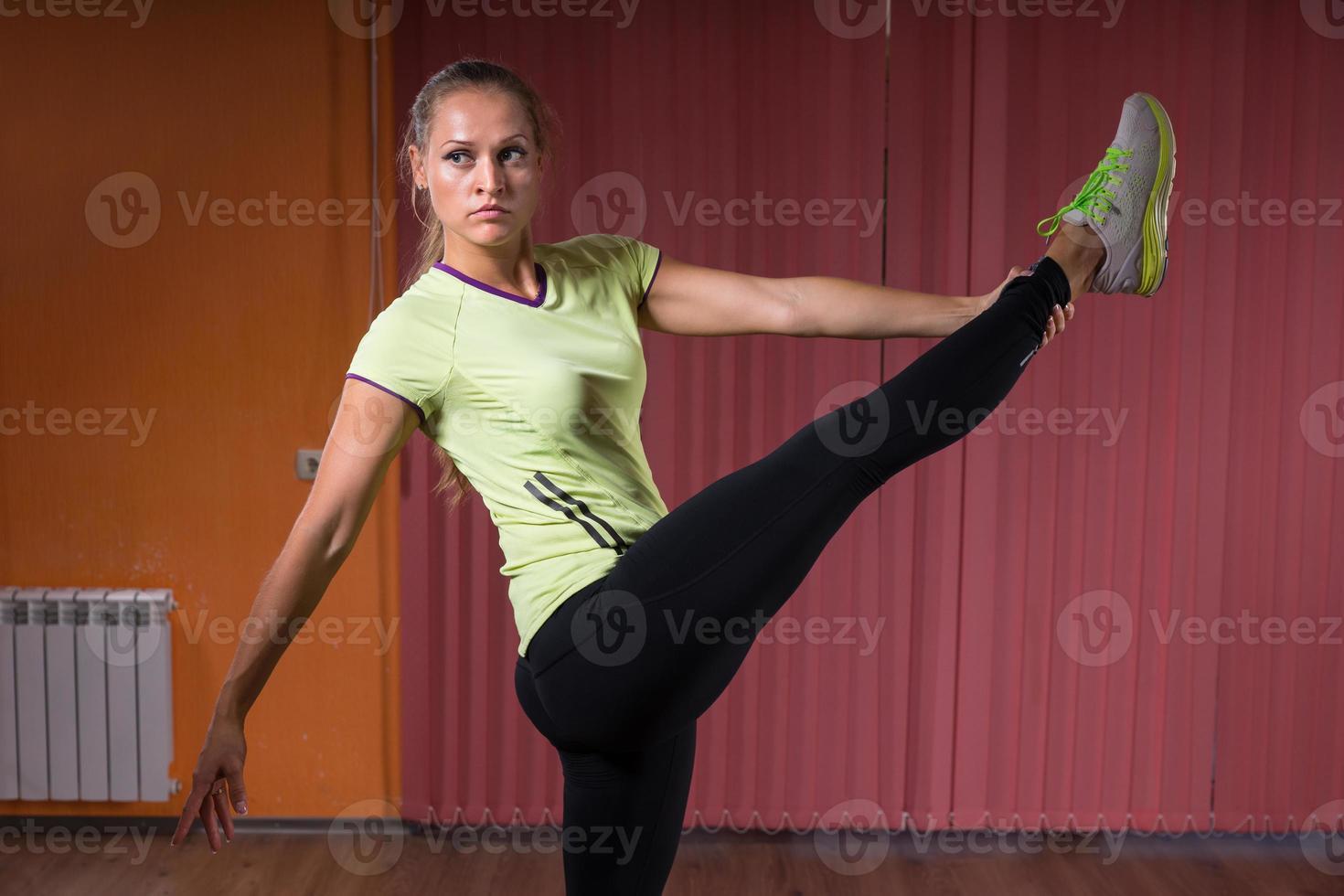 adatta giovane donna che allunga la gamba in aria foto