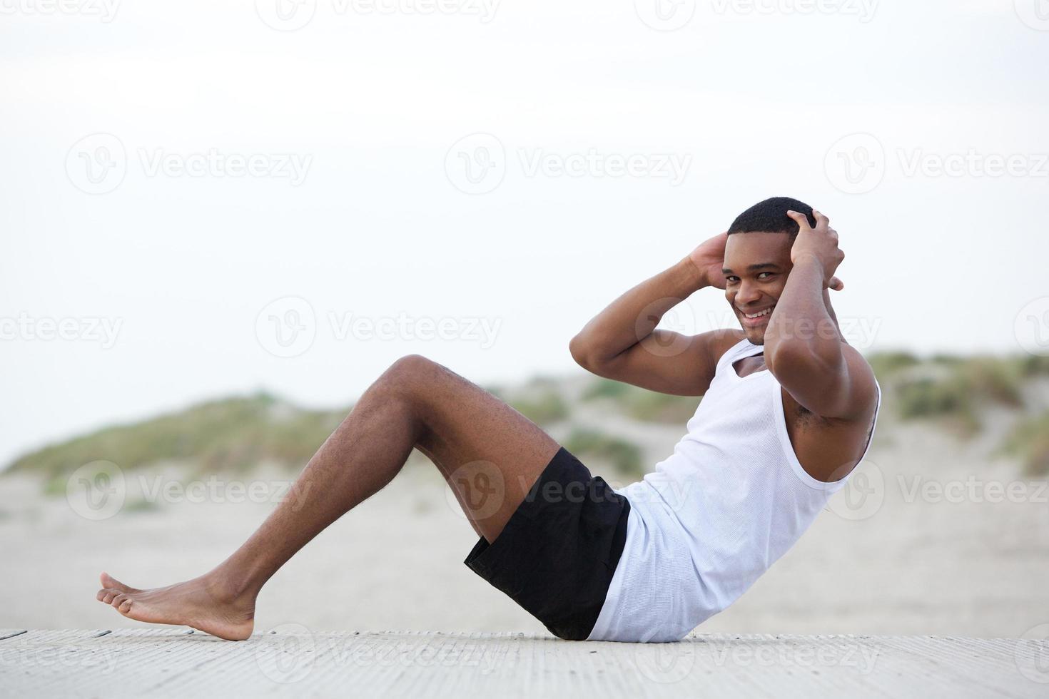 giovane in buona salute che fa sit up in spiaggia foto
