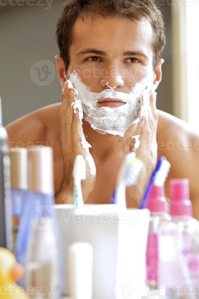 riflesso del giovane uomo in specchio applicando la crema da barba foto