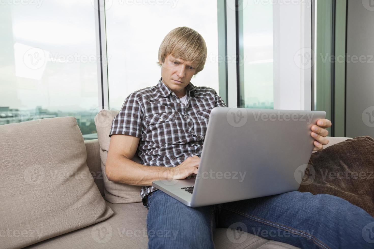 uomo serio dell'metà di-adulto che per mezzo del computer portatile sul sofà a casa foto