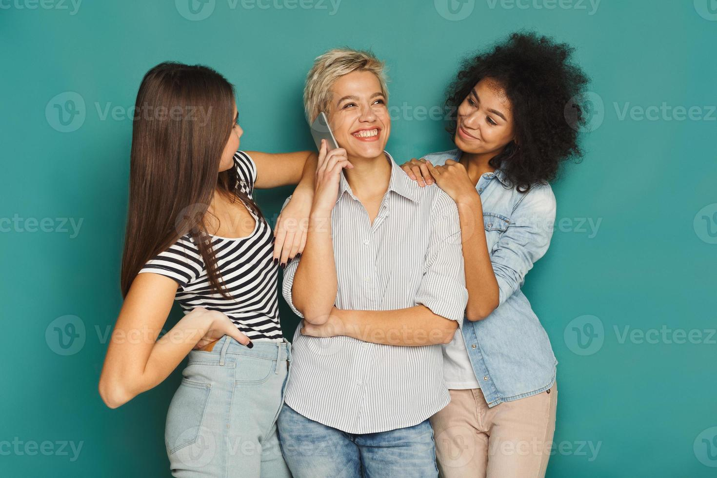ragazze che ascoltano la sua amica parlare al cellulare foto