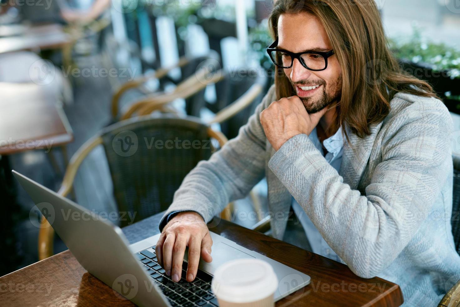 uomo che lavora al notebook da caffè all'aperto foto