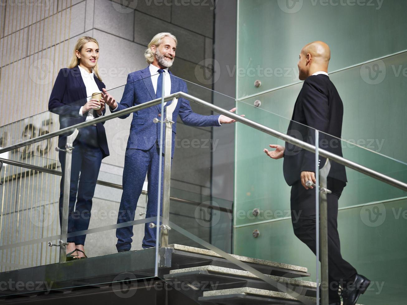 gente corporativa che accoglie favorevolmente il visitatore sulle scale foto