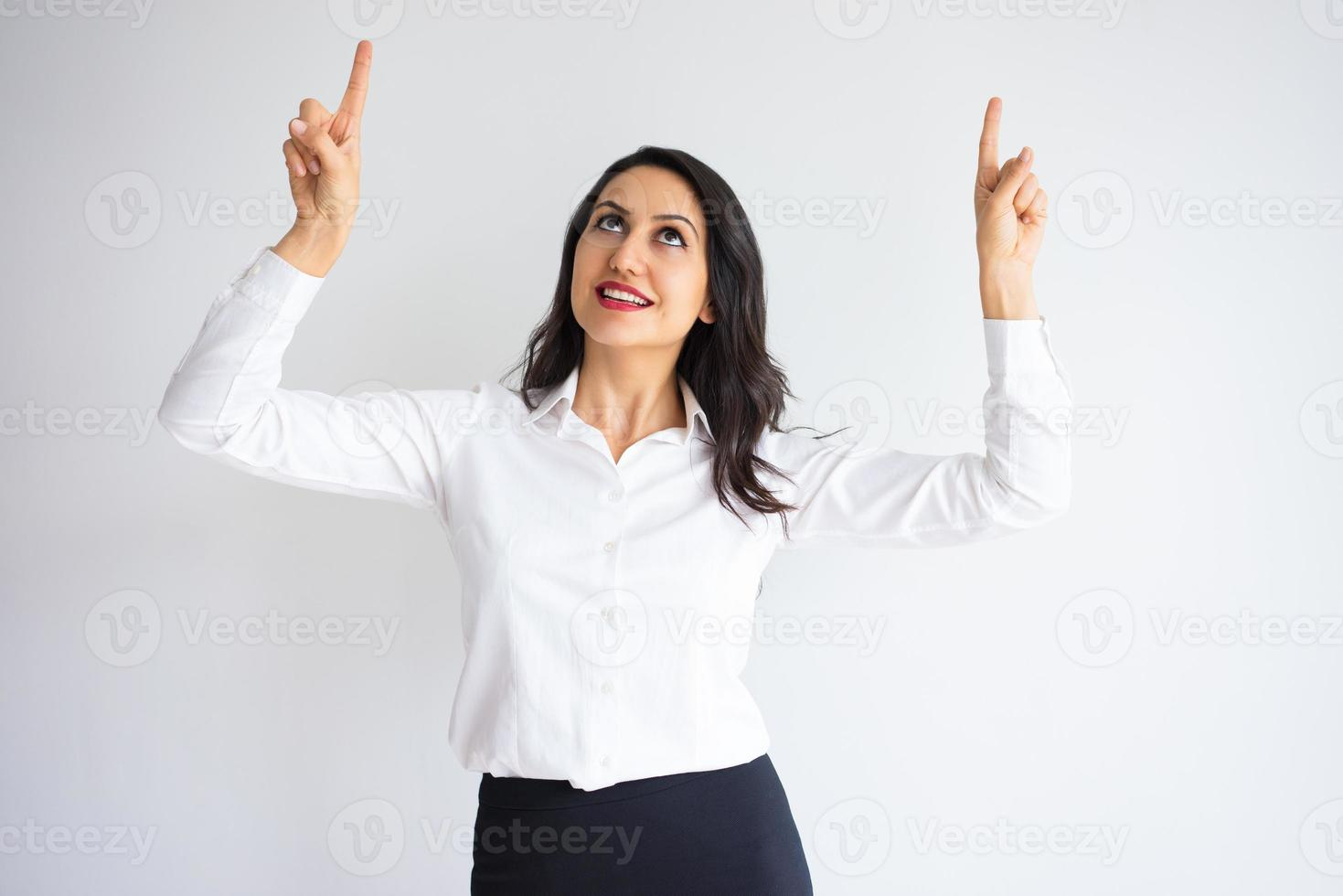 sorridente bella donna d'affari che punta verso l'alto foto