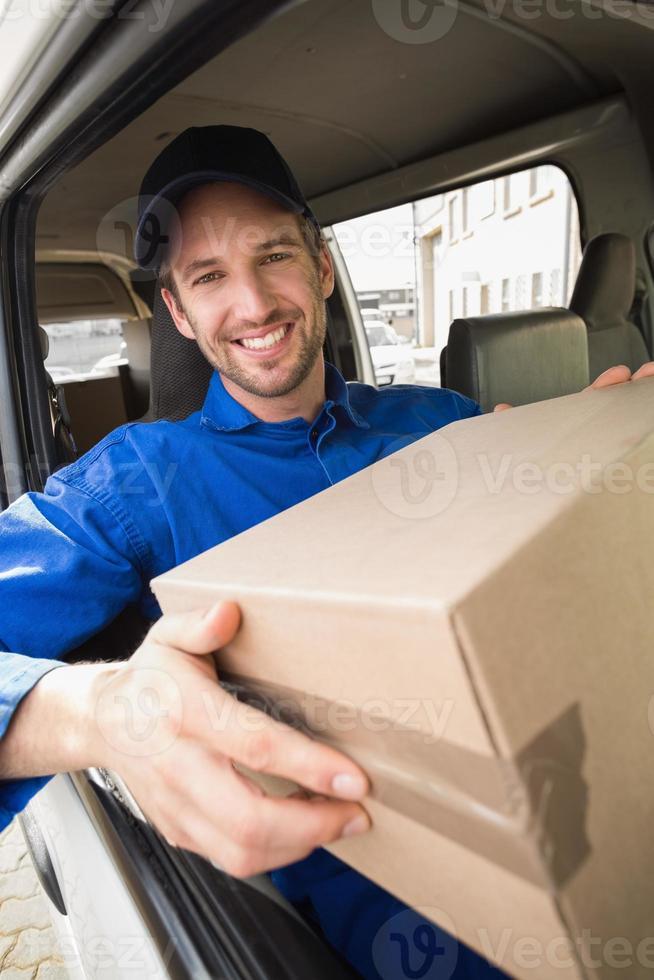 autista di consegna che tiene il pacco nel suo furgone foto