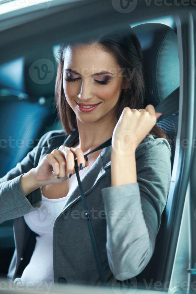 la giovane donna chiude la cintura di sicurezza foto