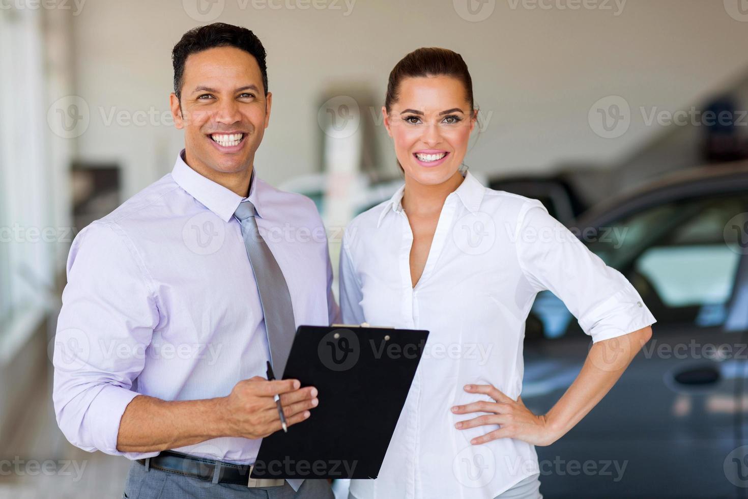 due operai in piedi all'interno dello showroom di auto foto