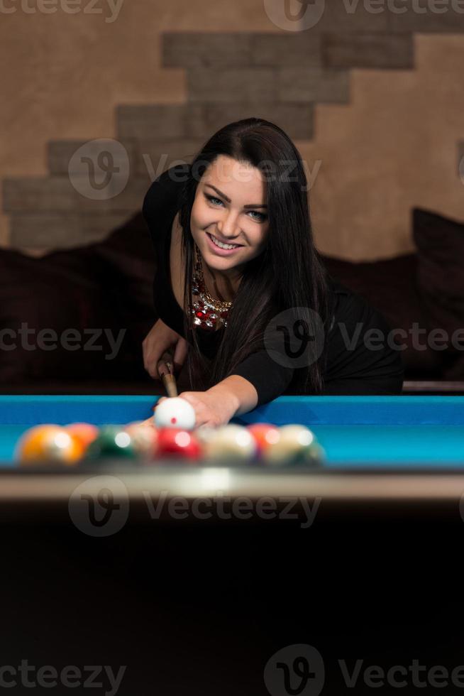 donna felice sorridente, giocare a biliardo foto