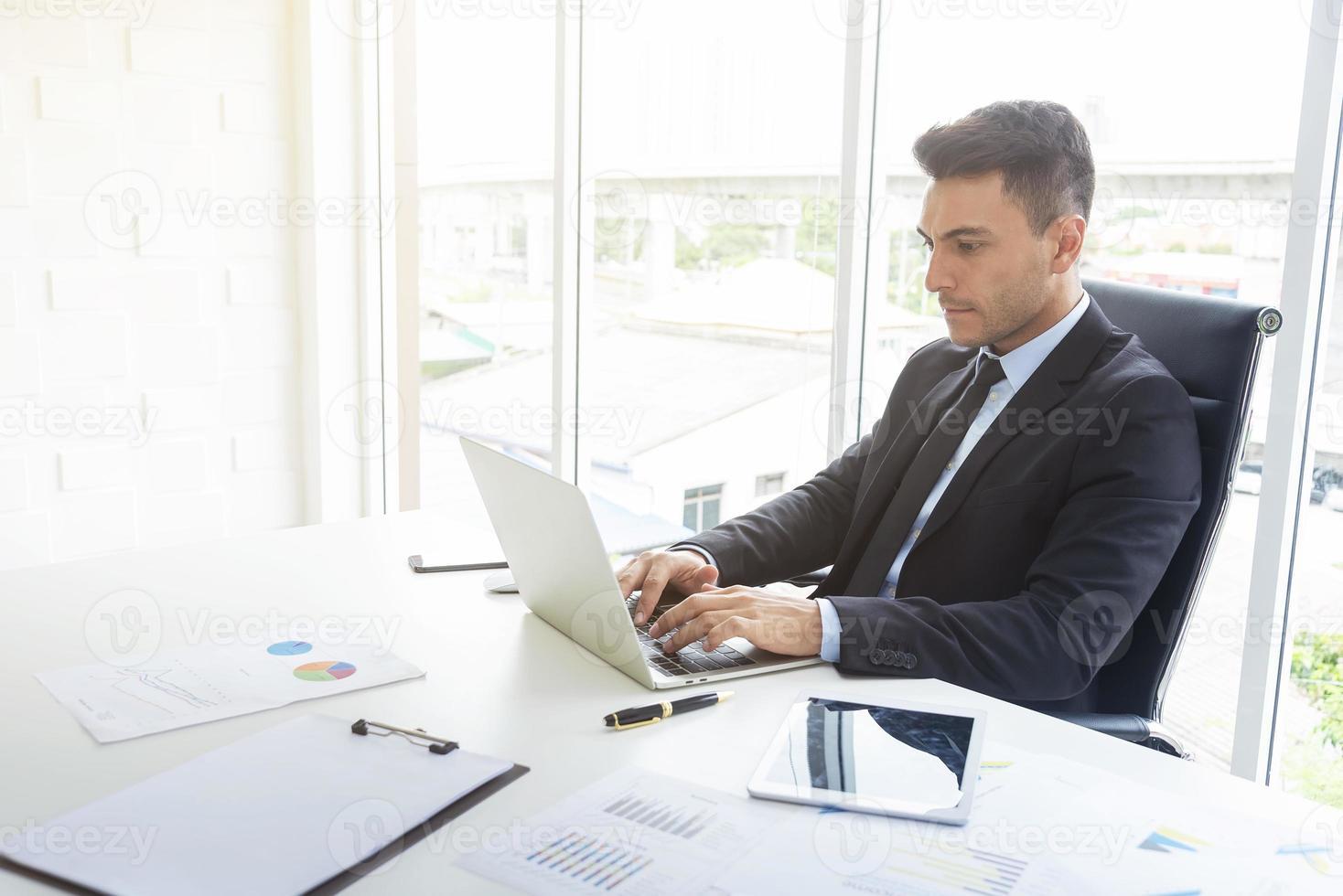 uomo d'affari bello che lavora allo scrittorio con il grafico del documento e del computer portatile in ufficio. concetto di tecnologia e uomo d'affari professionale. foto
