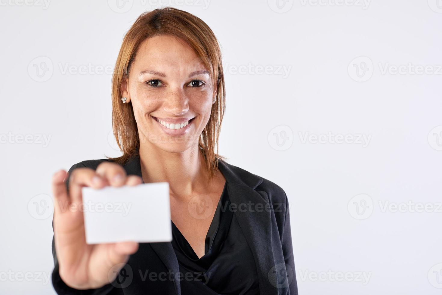 donna sorridente di affari di Latina che ostacola carta in bianco foto