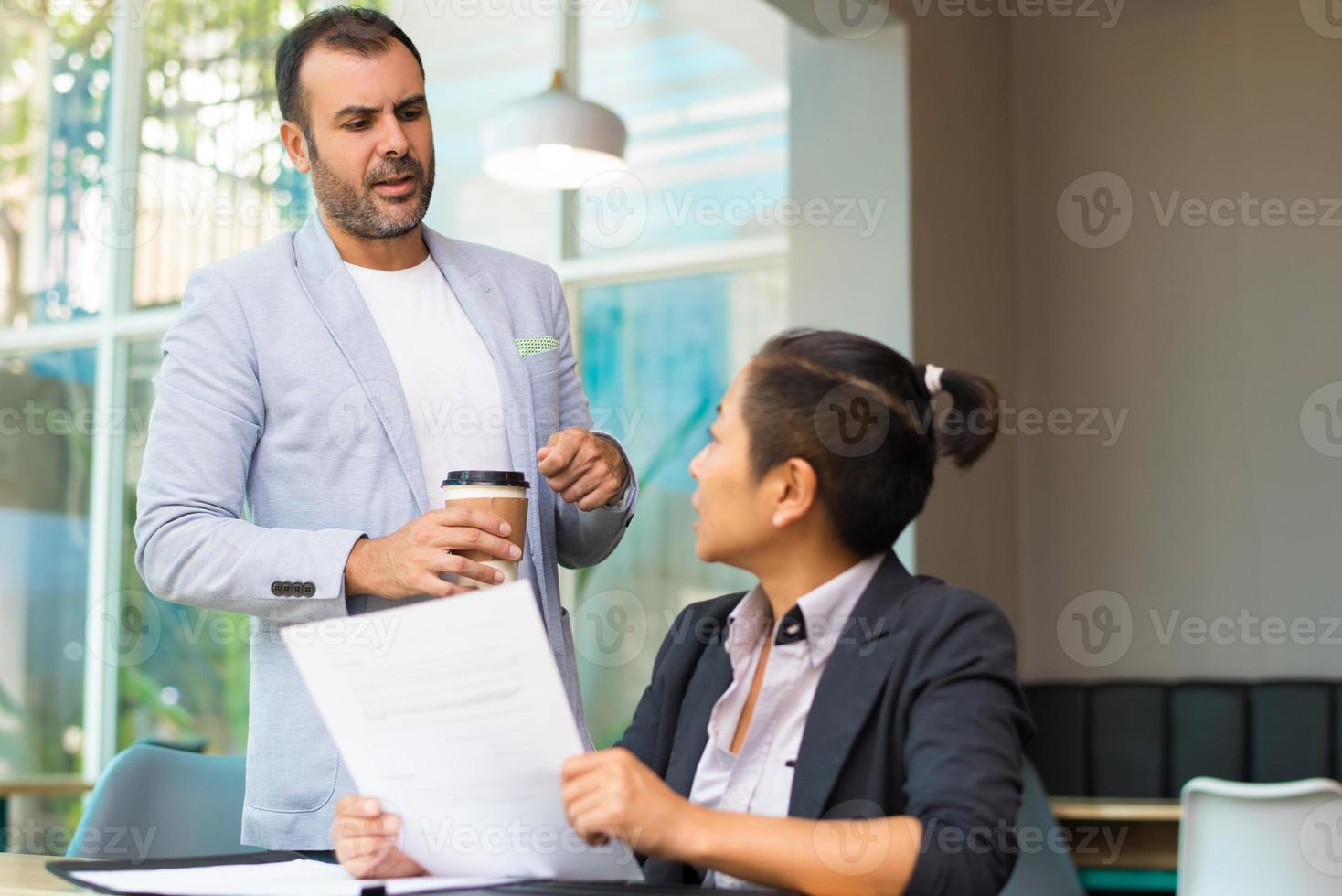 uomo d'affari ispanico pensieroso con una tazza di caffè a parlare con il manager foto