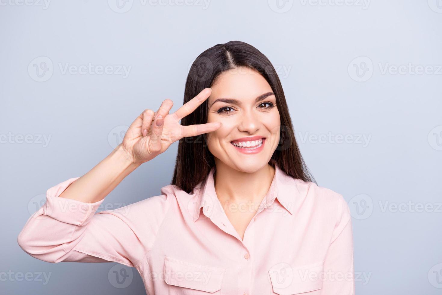 Ritratto di giocosa, funky, simpatica, carina, affascinante donna di buon umore gesticolando v-sign con due dita vicino occhio guardando la telecamera isolata su sfondo grigio foto
