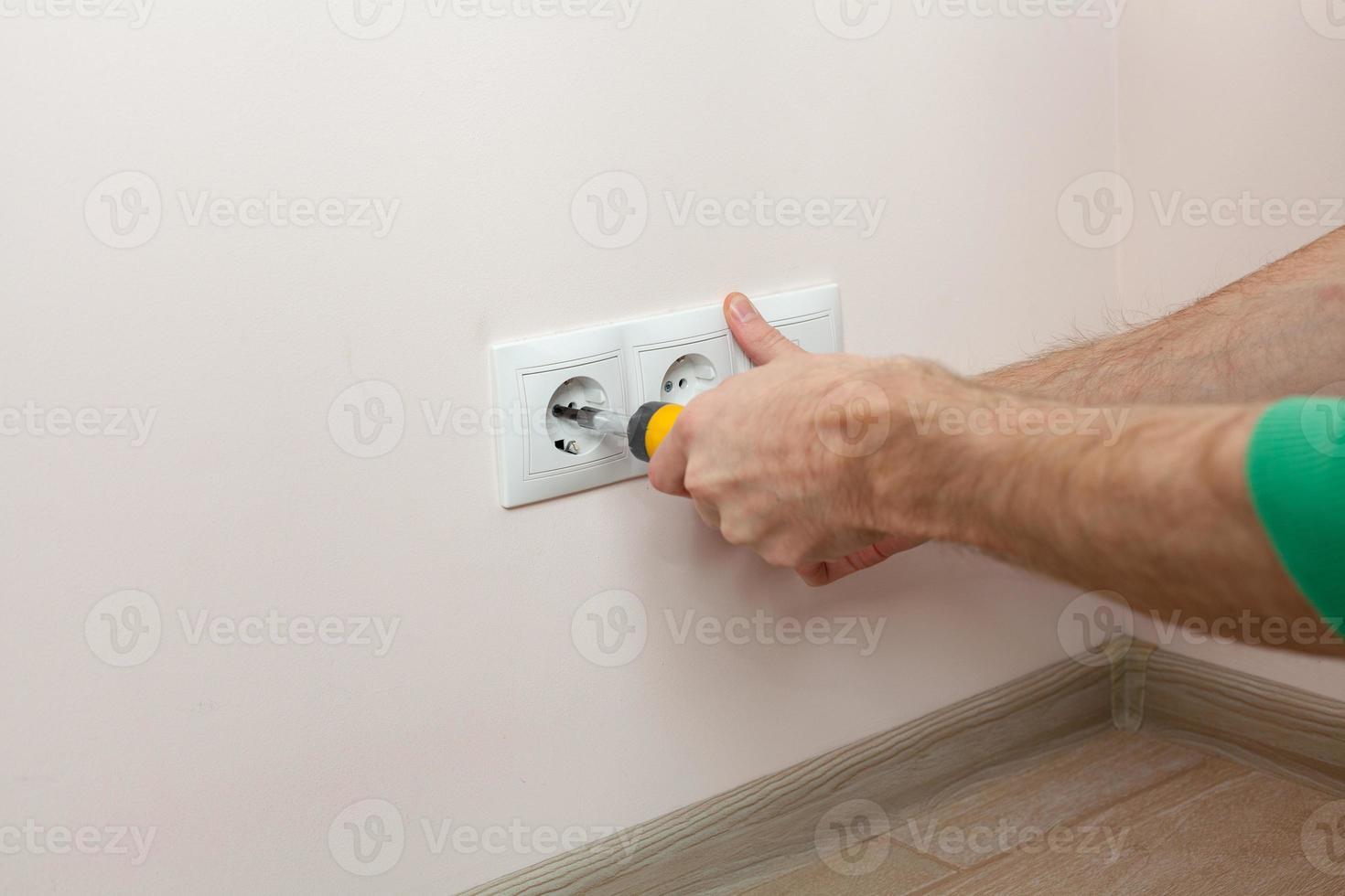 le mani di un elettricista che installa una presa a muro foto