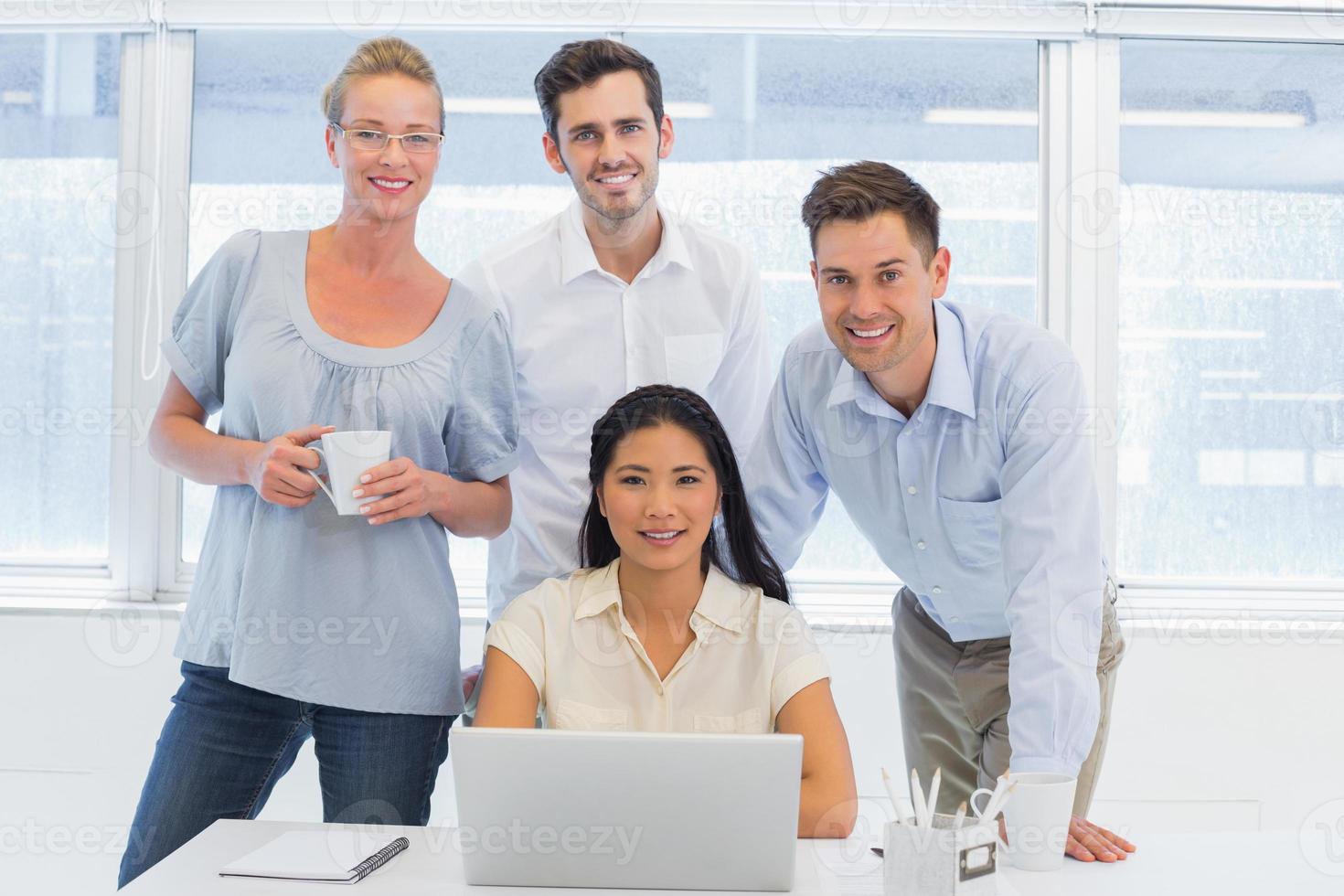 squadra di affari casuali che per mezzo del computer portatile insieme allo scrittorio foto