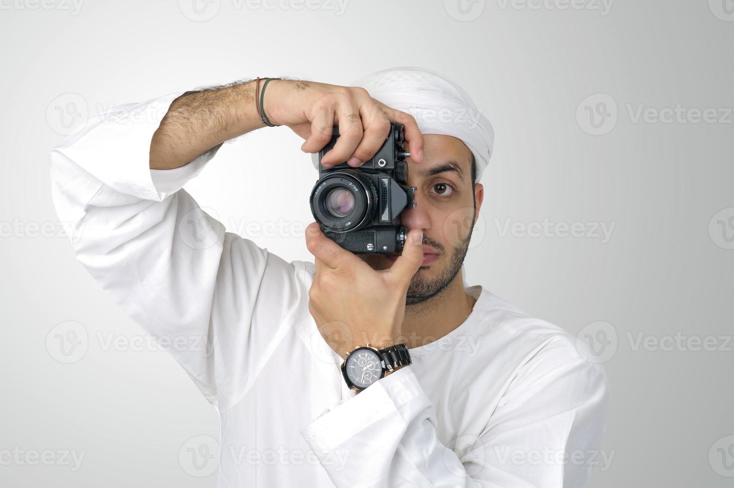 giovane uomo arabo usando tenendo la sua macchina fotografica pronta a sparare, foto
