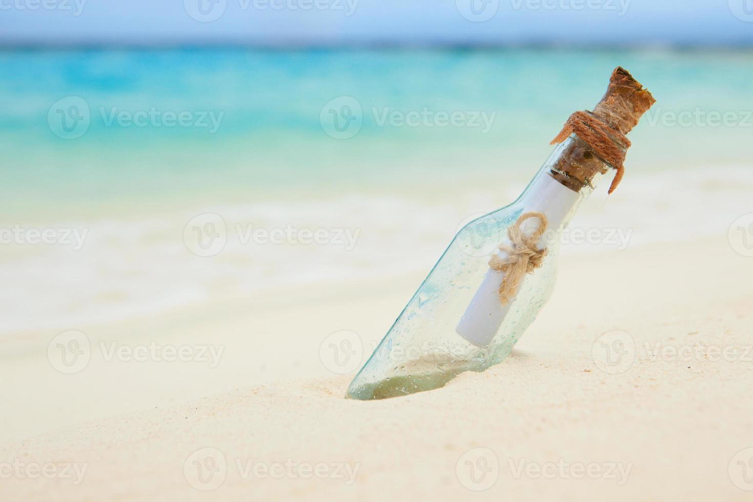 lettera in una bottiglia sulla spiaggia foto