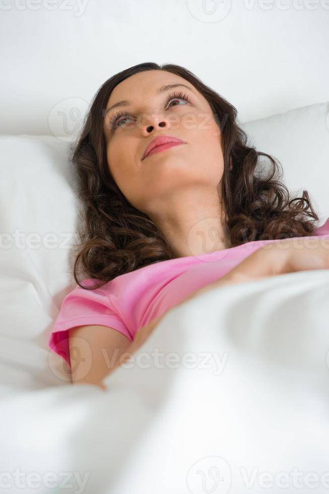 donna letto guardando sognando verso l'alto foto