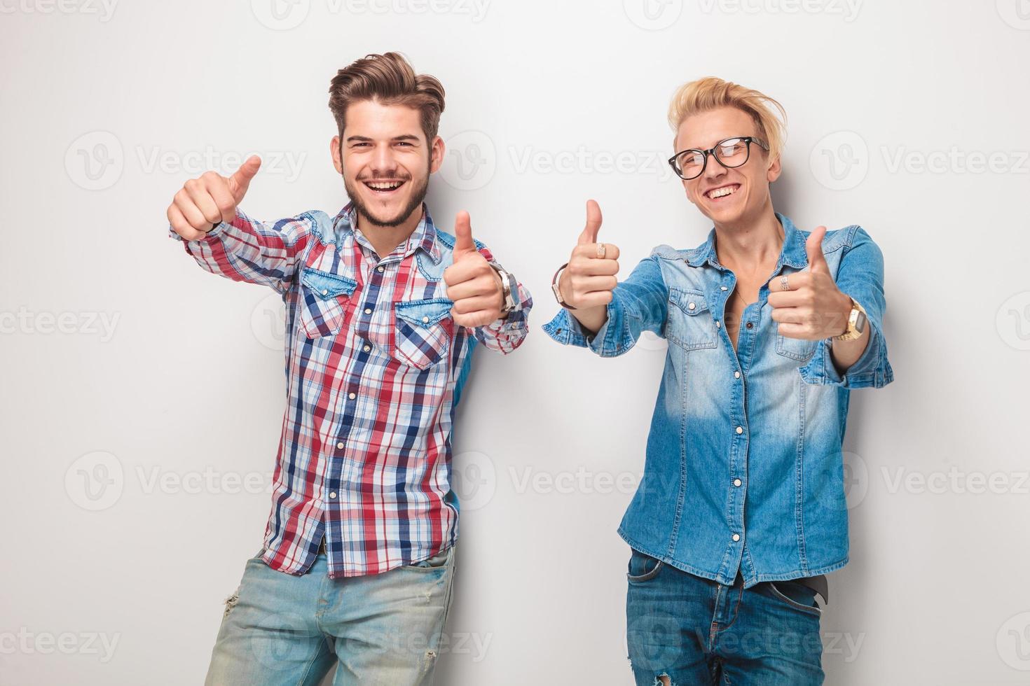 due giovani uomini casuali felici che fanno il segno giusto foto
