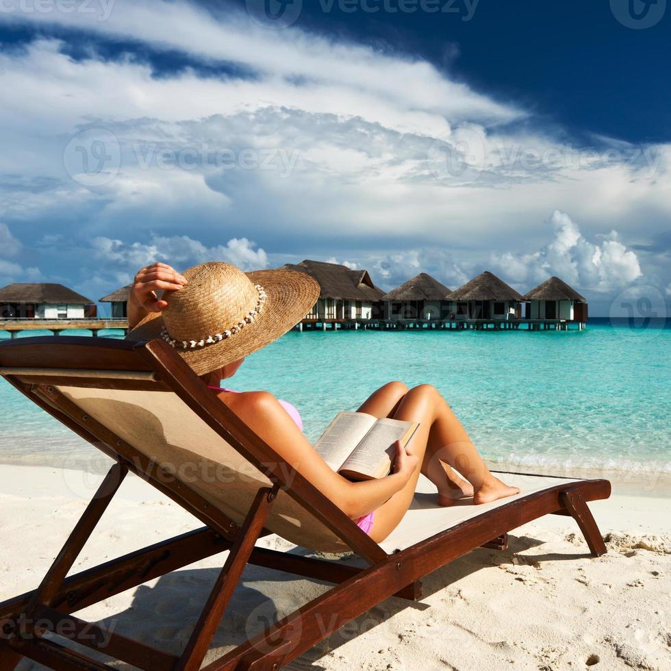 giovane donna che legge un libro in spiaggia foto