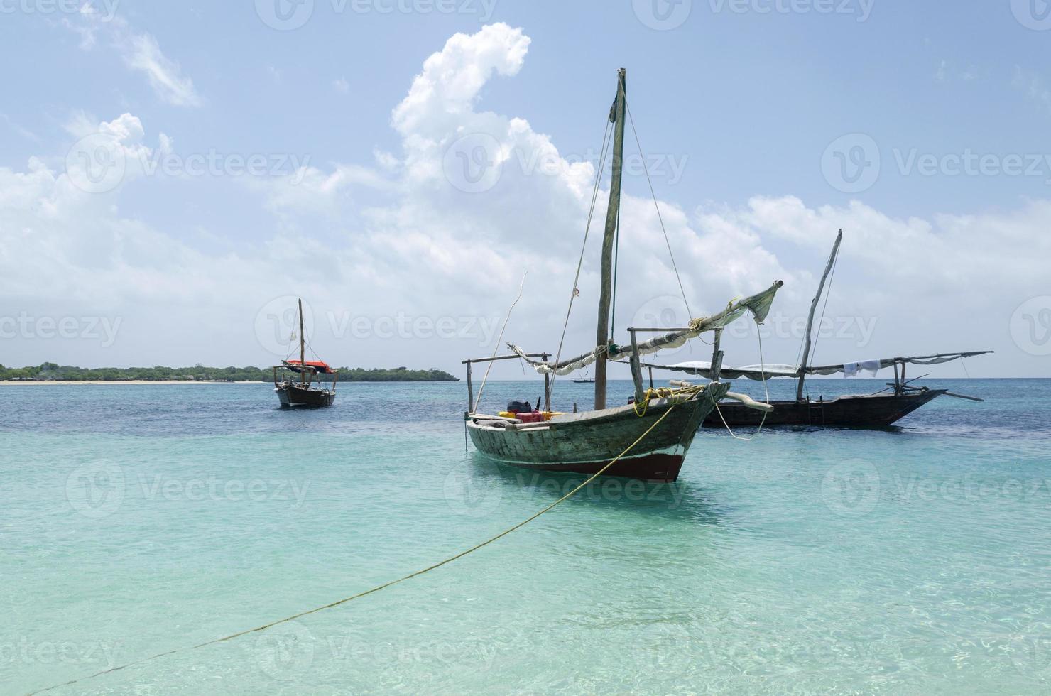 barca di legno sull'acqua turchese a zanzibar foto