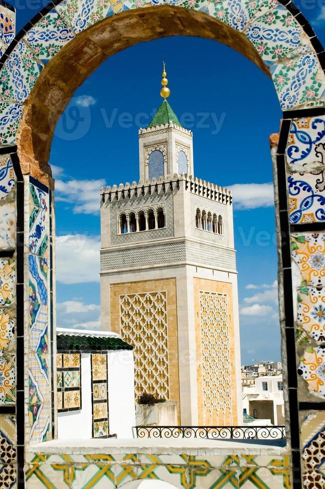 torre della moschea - incorniciata con arco ornamentale a tunisi foto
