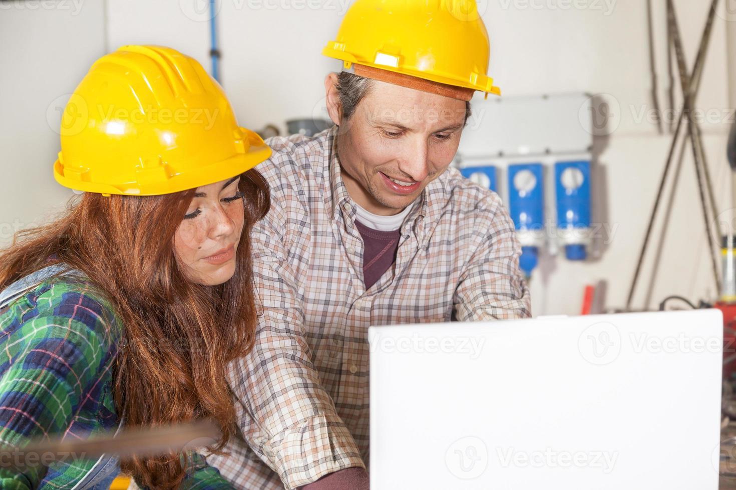 una coppia di ingegneri consulta il computer in un'acciaieria foto