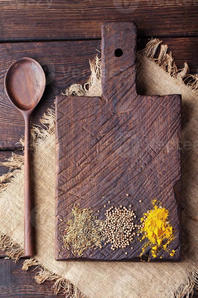 tagliere di legno e cucchiaio con spezie: cumino, carry, curcuma. foto