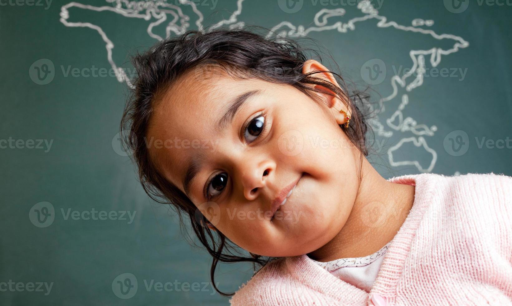 piccola ragazza prescolare indiana sveglia davanti alla mappa di mondo foto