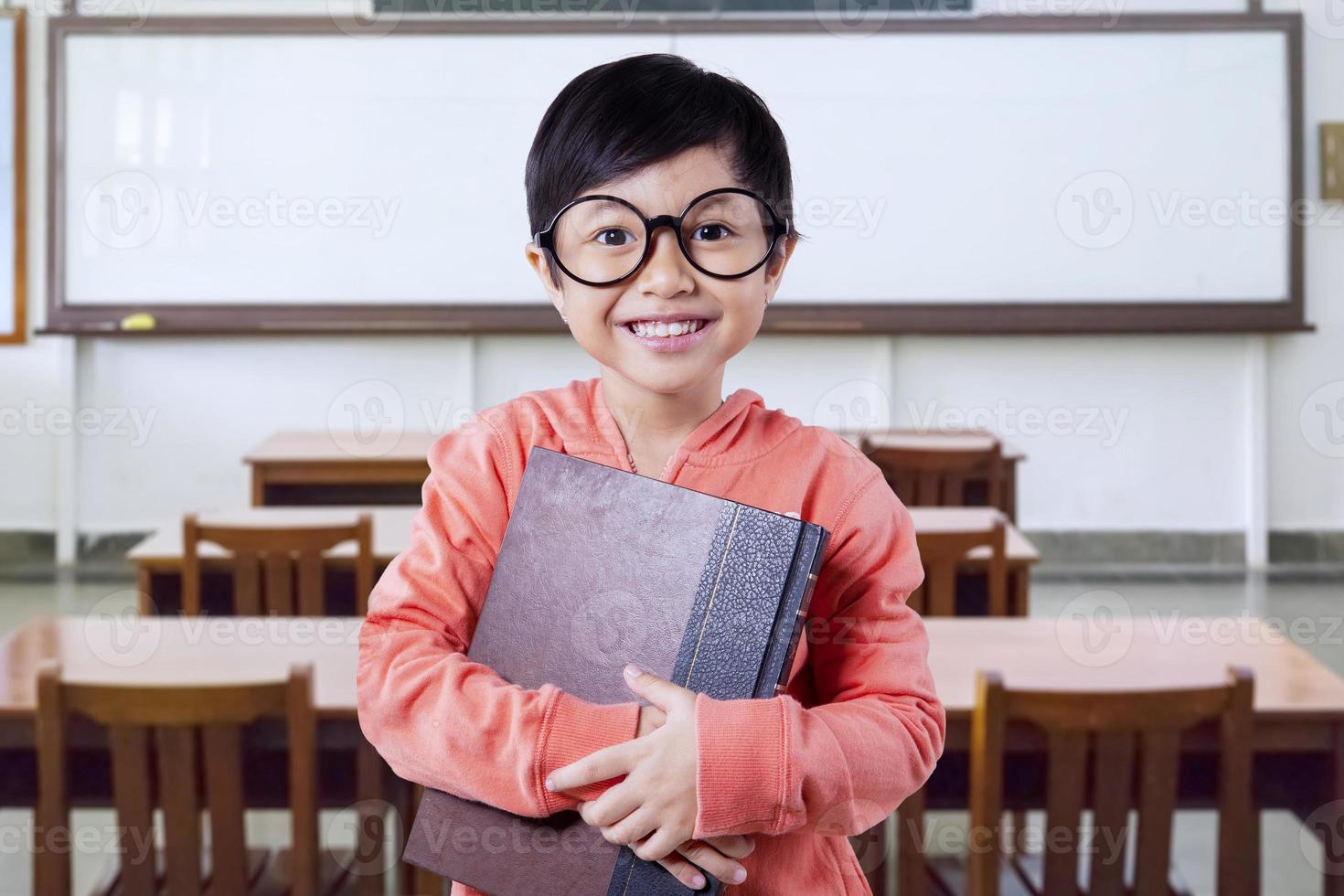 piccola studentessa con un libro in classe foto