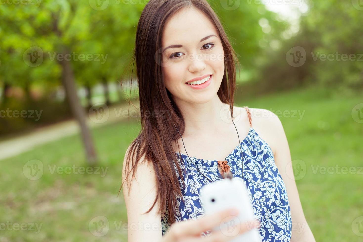 giovane donna asiatica che per mezzo dello Smart Phone all'aperto foto