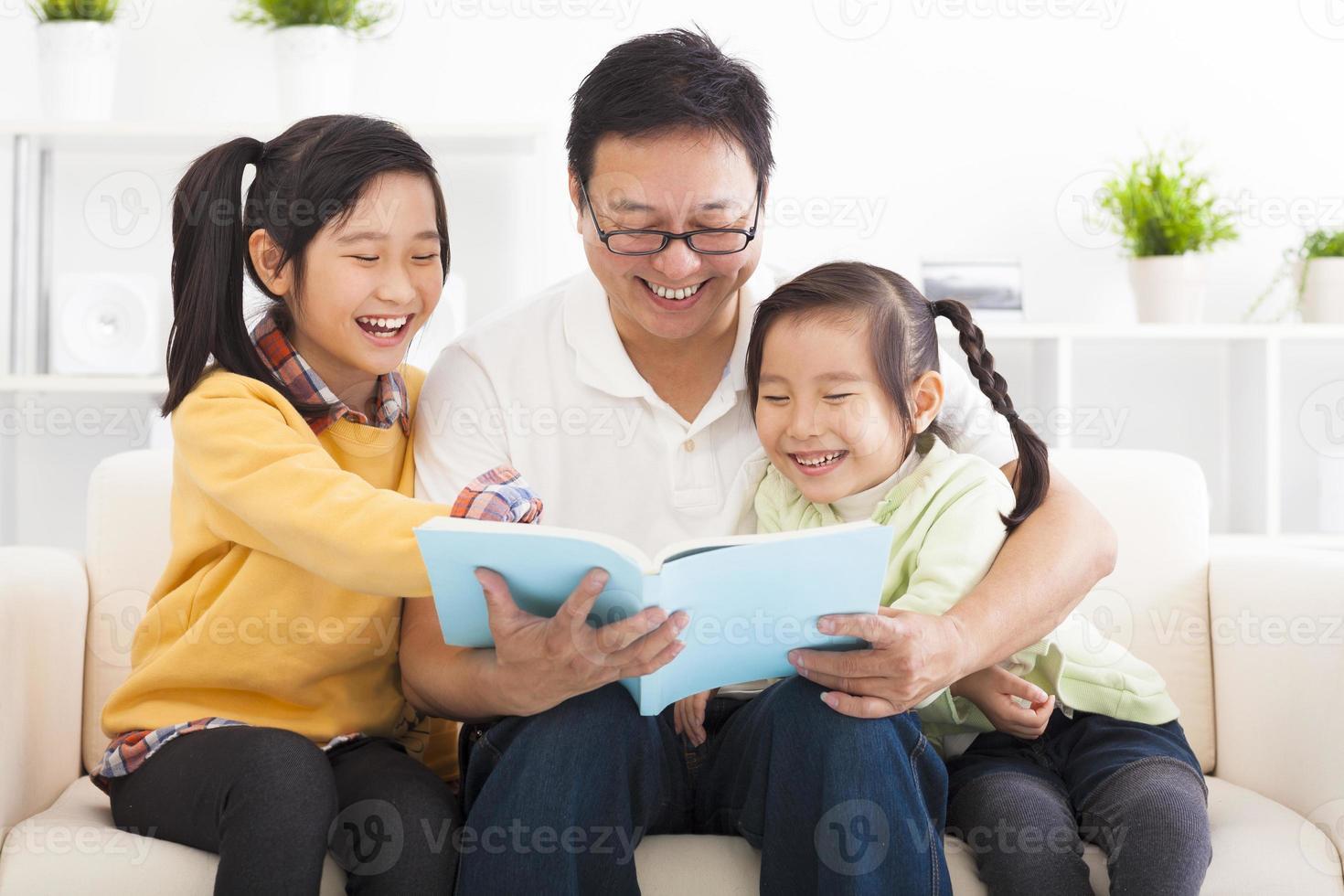 padre felice ha letto il libro per i bambini foto