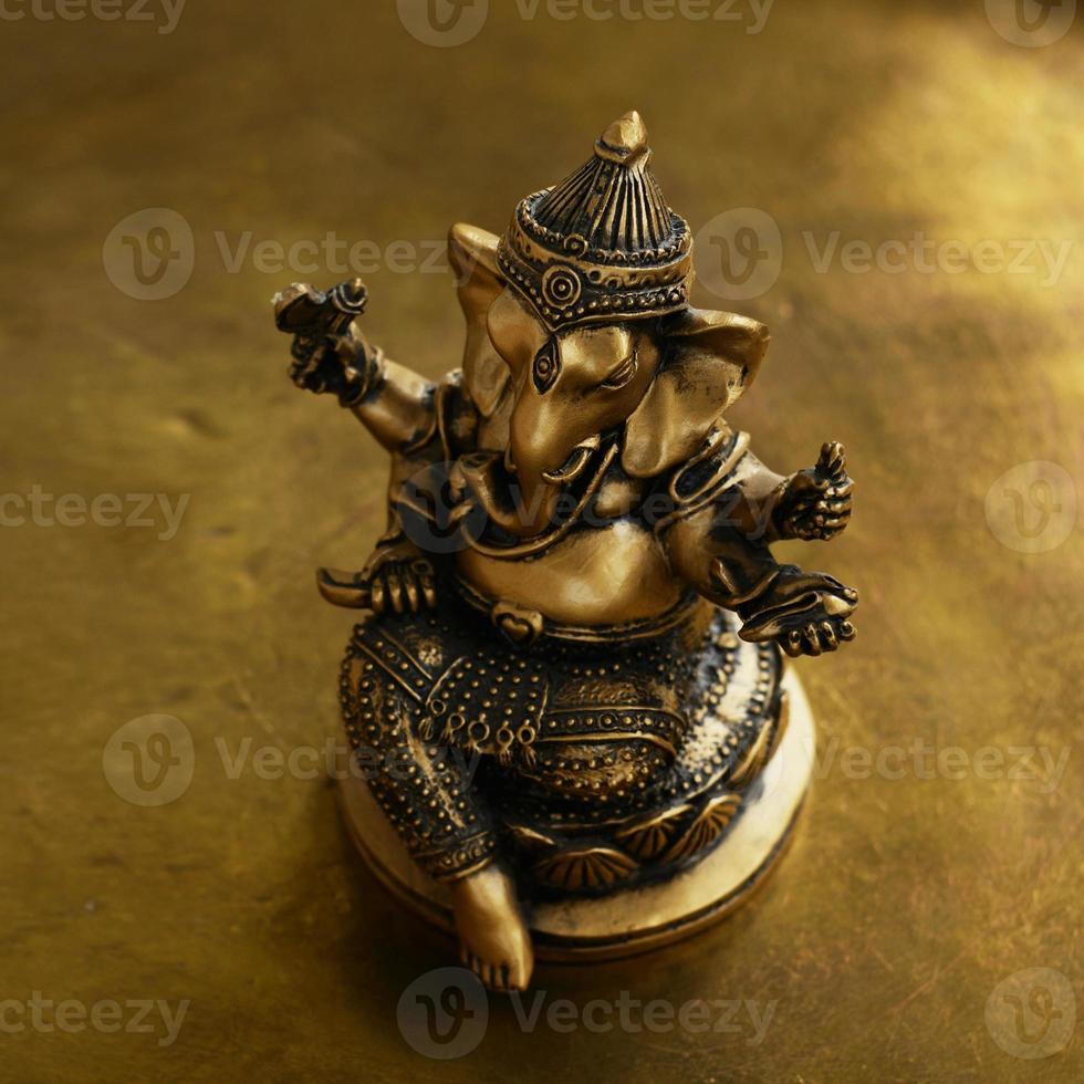 statuetta in bronzo ganesh su sfondo dorato foto