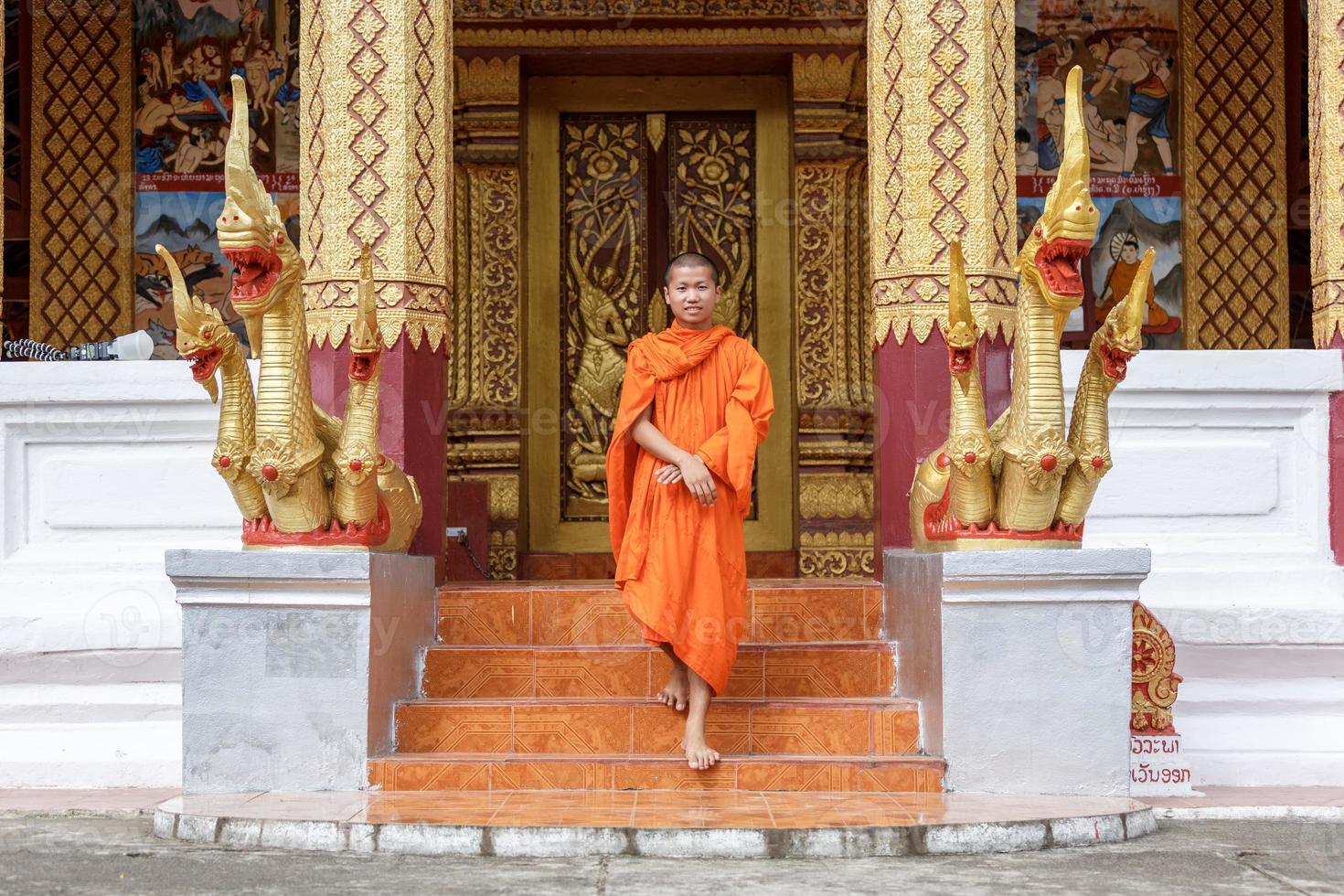 giovane monaco buddista che cammina davanti al monastero foto