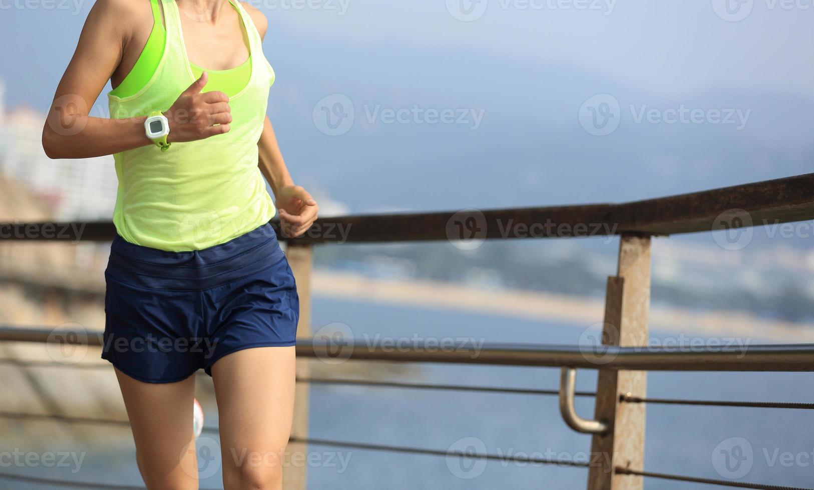 donna di sport fitness in esecuzione sul lungomare in legno foto