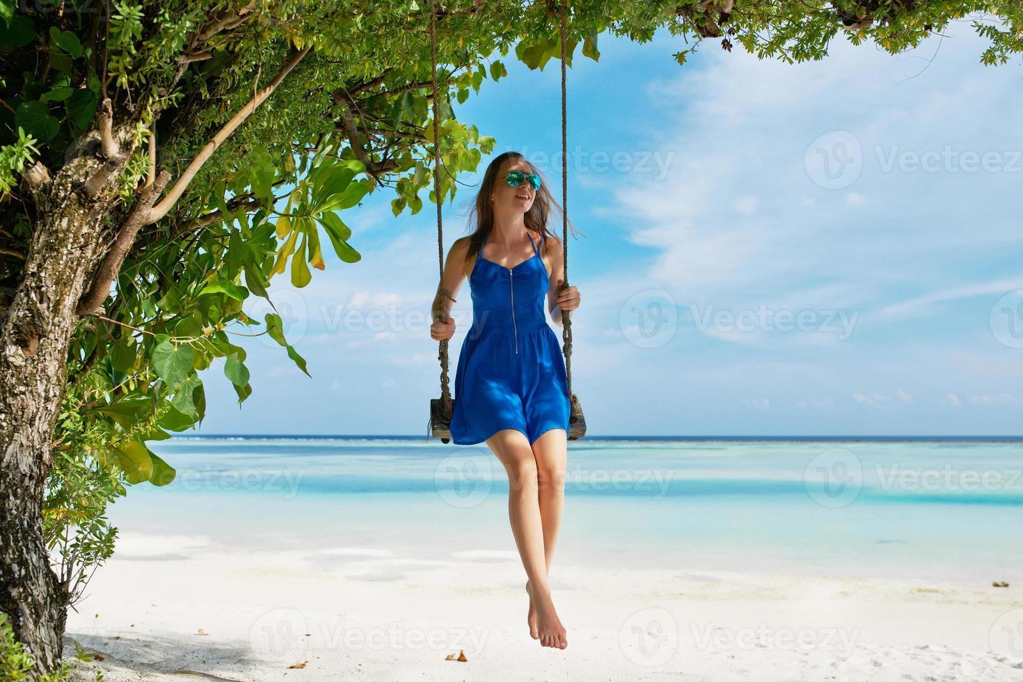 donna in abito blu oscillante in spiaggia foto