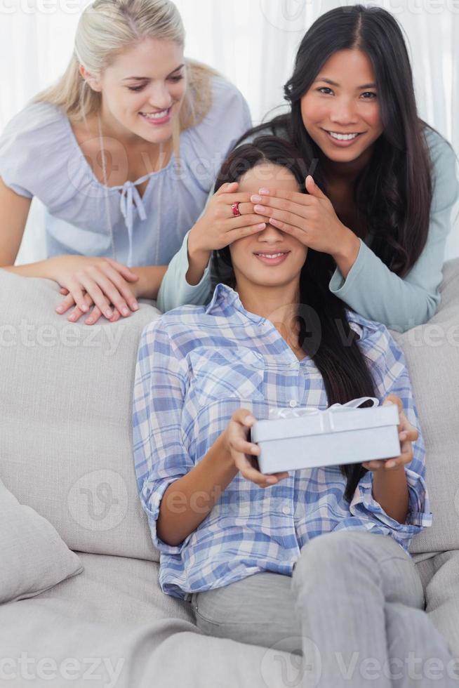 amici che sorprendono bruna con un regalo foto