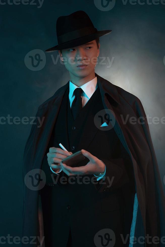 uomo di moda gangster asiatico 1940 retrò spaventoso. tenendo la scatola di sigarette. foto
